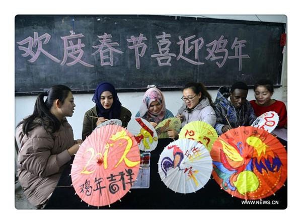 Int students paint patterns on umbrellas to greet Year of Rooster